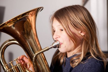 young girl blowing horn
