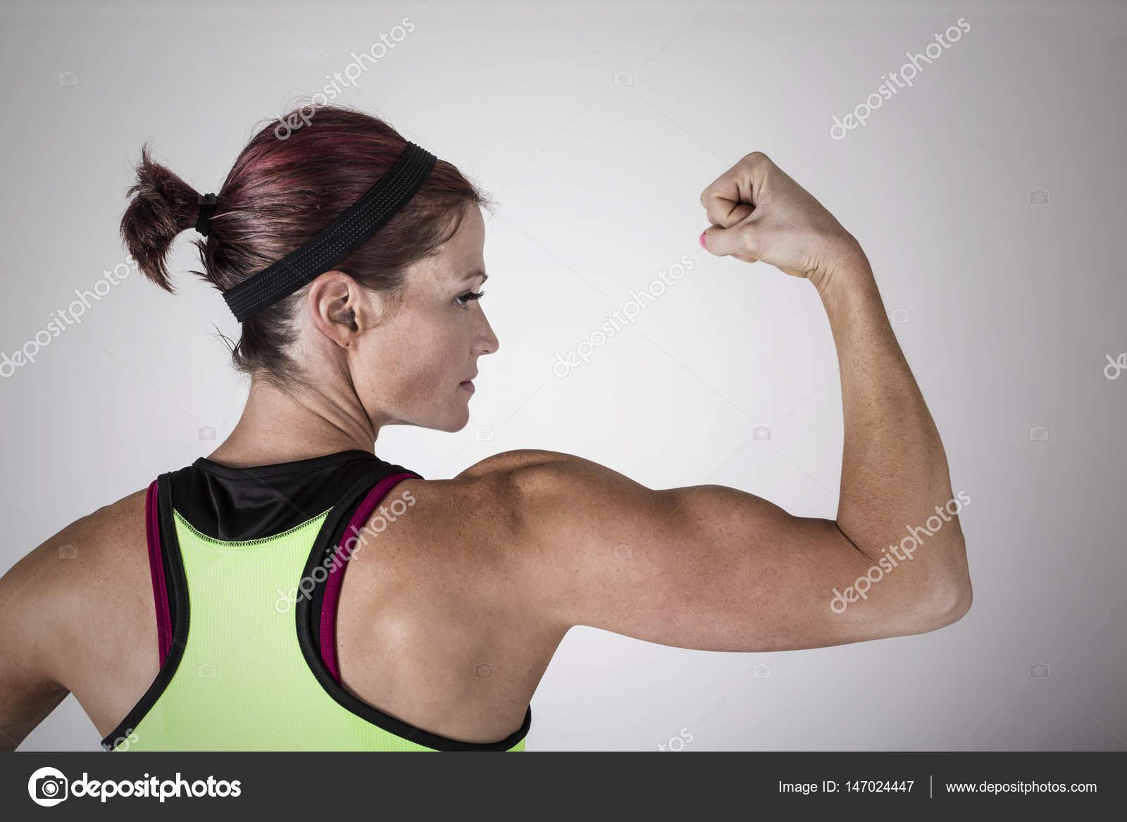 Schöne starke muskulöse Frau, die ihren Bizeps und Arm Muskeln ...