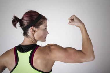 Beautiful strong muscular woman flexing her biceps and arm muscles.