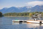 Fotografie Krásné letní scénu motorového člunu zaparkovaná u přístaviště lodí na krásné, malebné horské jezero. Modrá obloha, modré hory, modrá voda