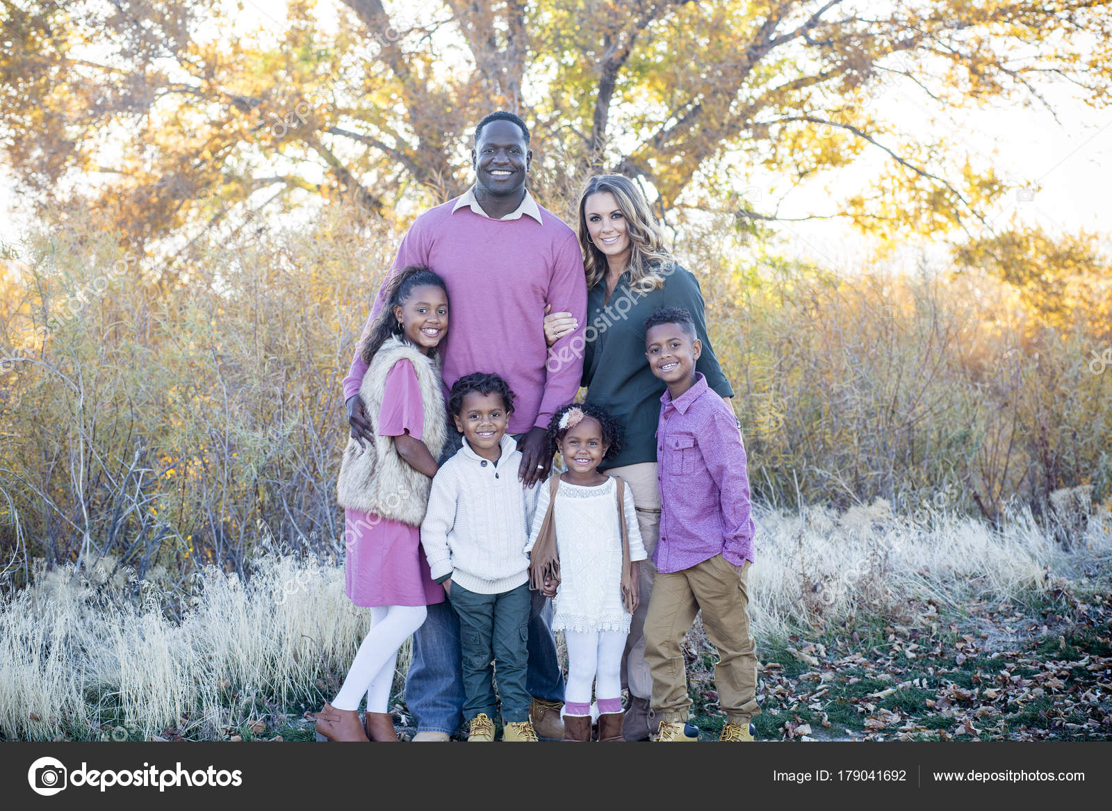 beautiful racial family portrait outdoors parents cute kids smiling