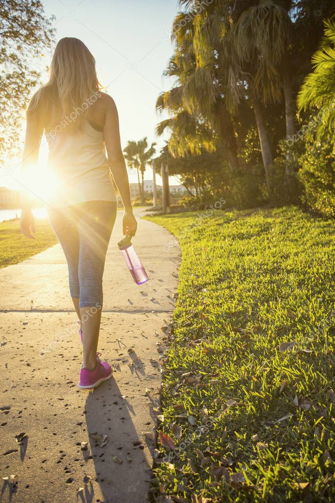 Beautiful blonde female jogger walking along a city park pathway on a sunny evening outdoors. Holding a water bottle. View of her legs and body from behind with a bright sun flare