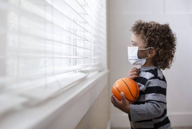 A young boy looking out the window wearing a protective facemark while seeking protection from COVID-19, or the novel coronavirus, by sheltering in place in his home. stock vector