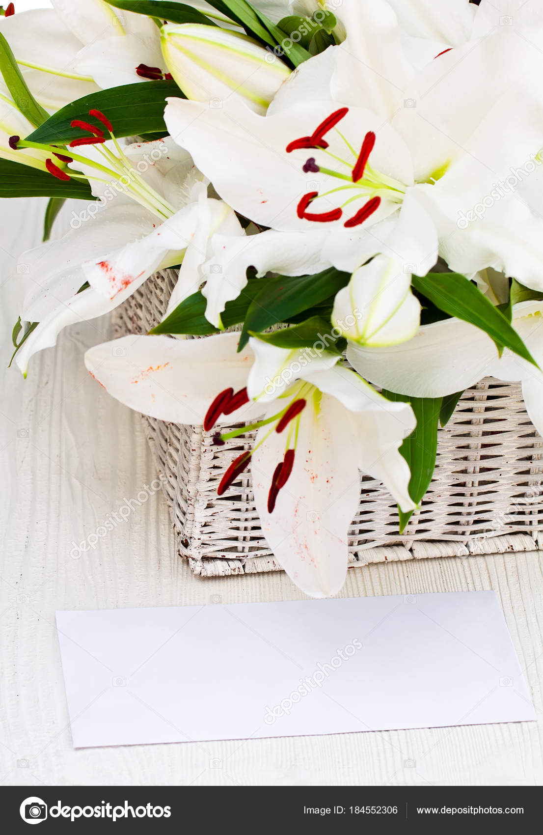 Old Basket With Lily Flowers Bouquet On Wooden Table With White