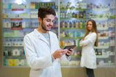 Portrait of pharmacist holding digital tablet in pharmacy, in th