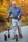Happy senior man with a walking disability enjoying a walk in an autumn park pushing her walker or wheel chair.