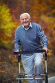 Photo Happy senior man with a walking disability enjoying a walk in an autumn park pushing her walker or wheel chair.