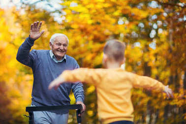 Cheerful disabled grandfather in walker welcoming his happy grandson