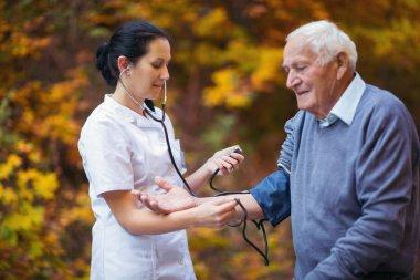 Nurse measuring old patient's blood pressure outdoor