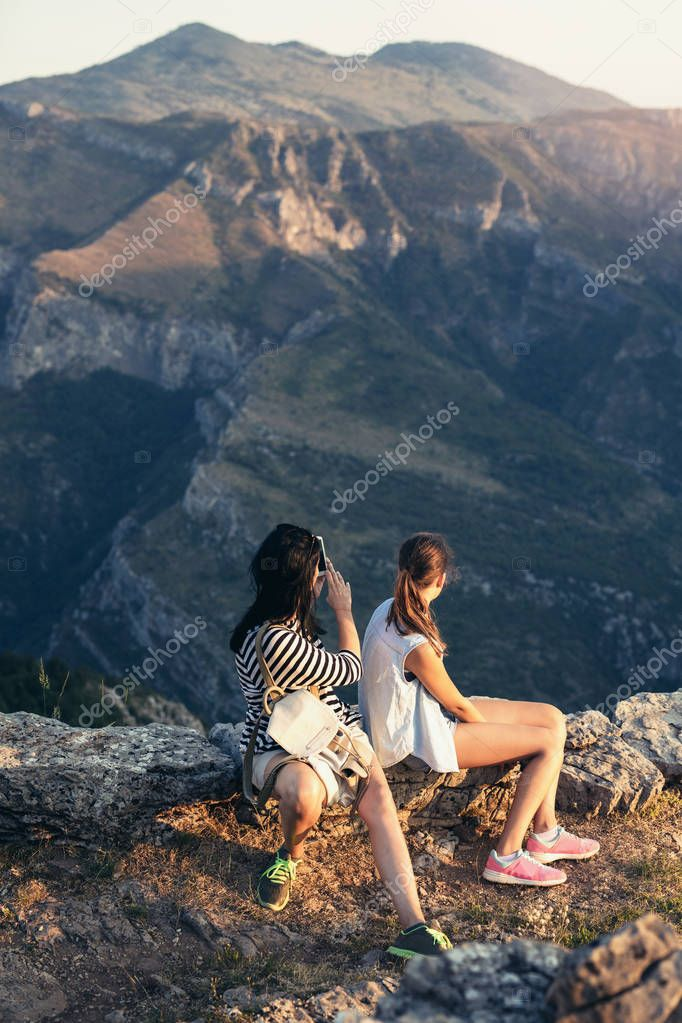 mother and daughter sitting on rock