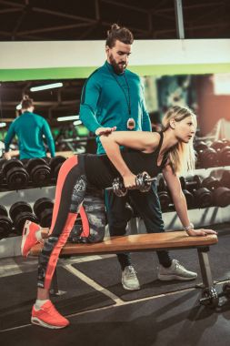 personal trainer helping woman at workout with heavy dumbbell