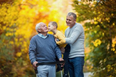 elderly grandfather, adult son and little grandson walking in autumn park