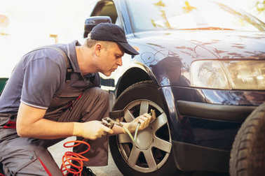 mechanic repairman at car tyre, fitting and balancing adjustment