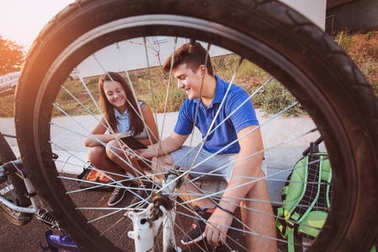 teenage boy repairing tire on bicycle, female friend sitting next to him, using digital tablet for instructions, summer outdoor photo