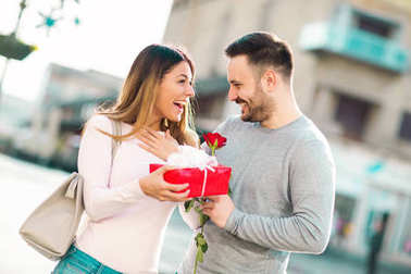 Man surprises woman with a gift in the city stock vector