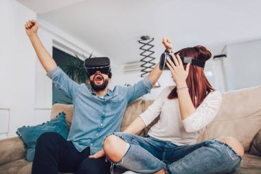 Young man and woman in casual clothes wear the virtual reality glasses are watching and showing imagine via the VR camera, Technology and innovation concept