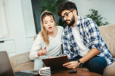 Woman and man doing paperwork together, paying taxes online on notebook pc