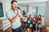 Gruppo di amici che giocano di karaoke a casa. Concetto di amicizia, intrattenimento domestico e persone
