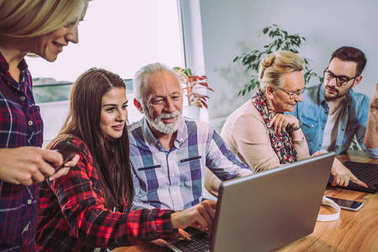 Young volunteers help senior people on the computer