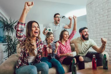 Happy friends or football fans watching soccer on tv and celebra