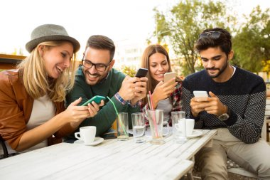 Group of four friends using smartphones, having fun and coffee together.
