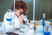 Nő scienist laboratóriumban. Fiatal tudós látszó átmenő egy Mikroszkóp laboratóriumban. Fiatal tudós csinál némely kutatás