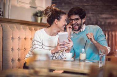 Young couple indoor in cafe using digital tablet