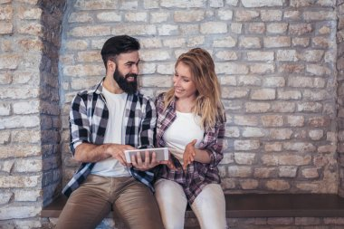 Happy young couple using digital tablet on brick wall background