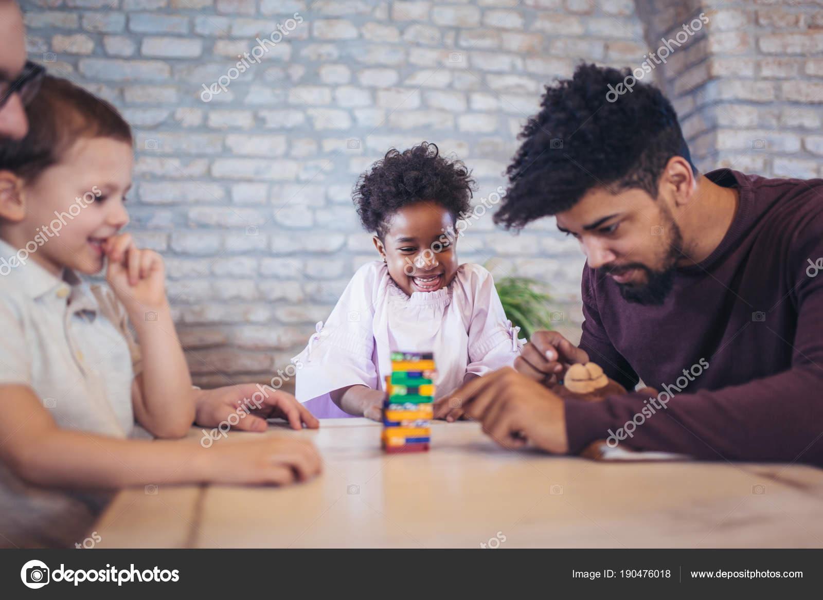 Dos Padres Con Los Ninos Jugando Jenga Juego Mesa Foto De Stock