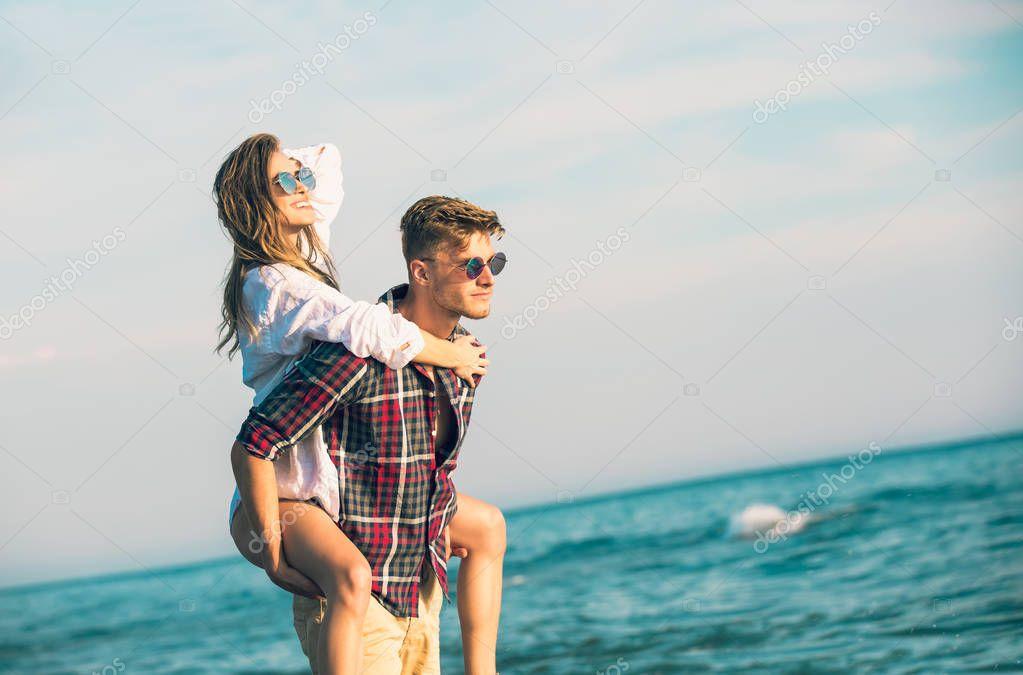 Happy couple in love on beach summer vacations. Joyful girl piggybacking on young boyfriend  having fun.