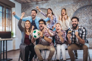 Happy friends or football fans watching soccer on tv and celebrating victory. Friendship, sport and entertainment concept.