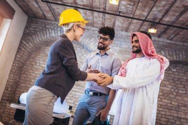 Cheerful group of business team welcoming Arabian businessmen