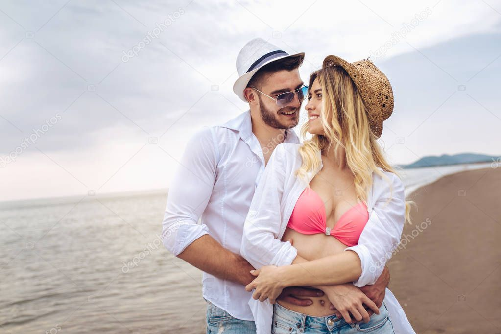 Lovers couple in love having fun dating on beach.