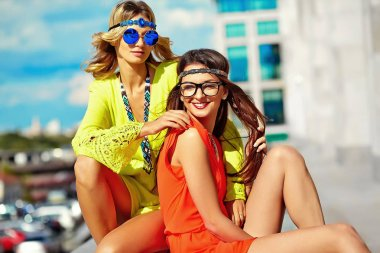 two young hippie women models in summer sunny day in bright colorful hipster clothes