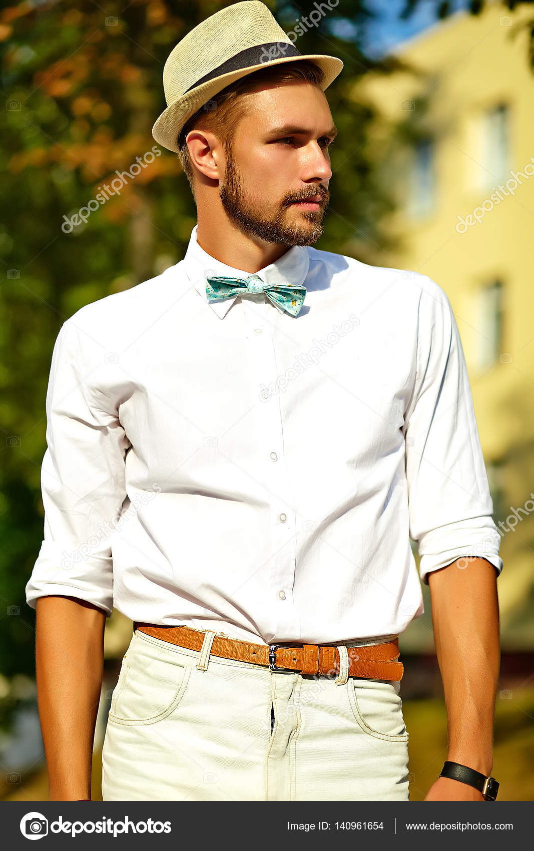 bde1d57453b2 Handsome hipster model man in stylish summer clothes posing on street  background in hat — Photo by ...