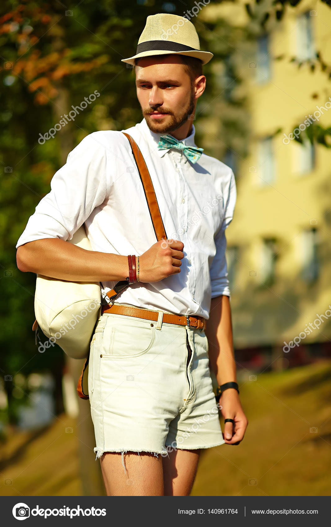 3d1bf6874bb3 Handsome hipster model man in stylish summer clothes posing on street  background in hat with bag — Photo by alexhalay