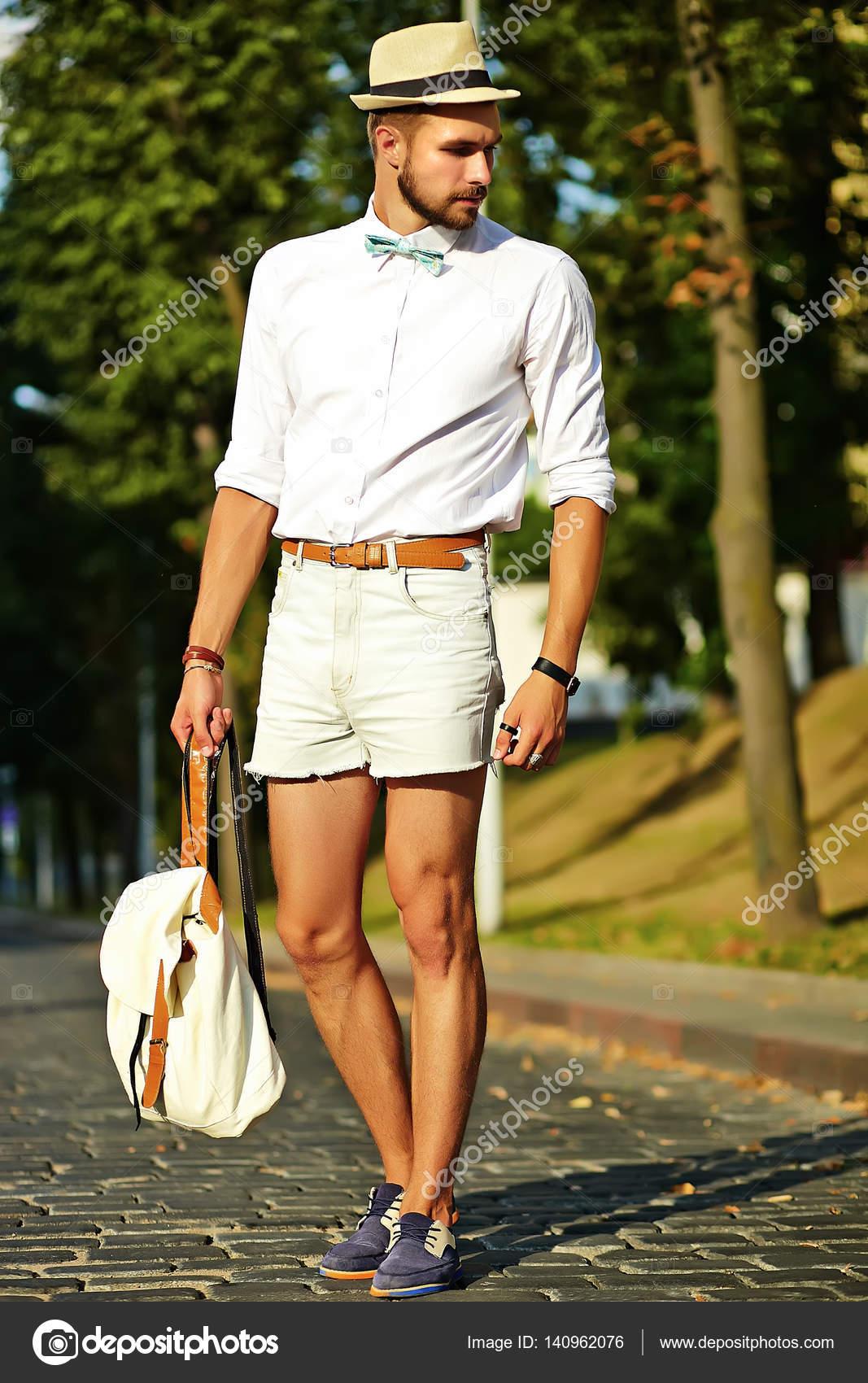 Hombre de hipster hermoso modelo en ropa de verano elegante posando sobre  fondo calle en sombrero con bolsa - ropa hipster hombre — Foto de alexhalay  — Foto ... 107e05e2cb4