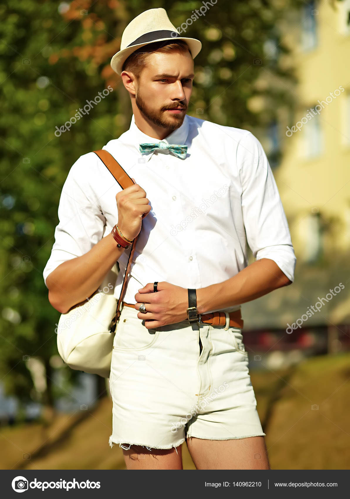 65b51453ef2b Handsome hipster model man in stylish summer clothes posing on street  background in hat with bag — Photo by ...