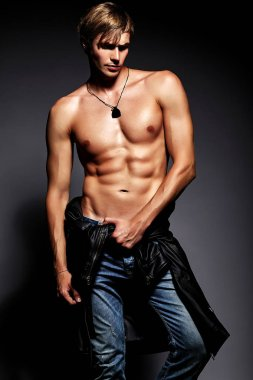 muscled fit male model man posing in studio showing his abdominal muscles in  leather jacket