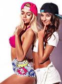 bruneta a blondýna modely v létě ležérní oblečení na barevné růžové pozadí