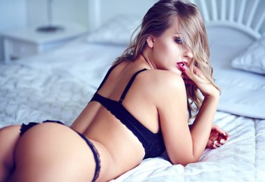 Blond model lying on bed