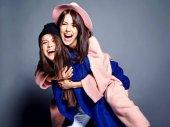Fotografie Módní portrét dvou usmívající se bruneta ženy modely v létě příležitostné bokovky kabát pózuje na šedém pozadí. Holky sobě drží na zádech