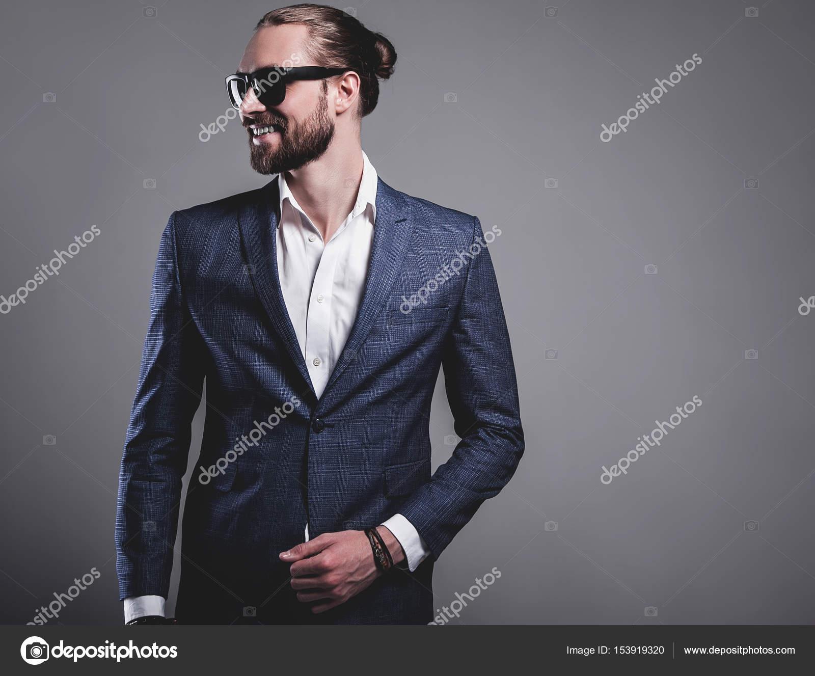 8676b6aa2 Retrato de hermosa moda hipster estilo empresario modelo vestido con elegante  traje azul en las gafas de sol posando sobre fondo gris en estudio — Foto  de ...