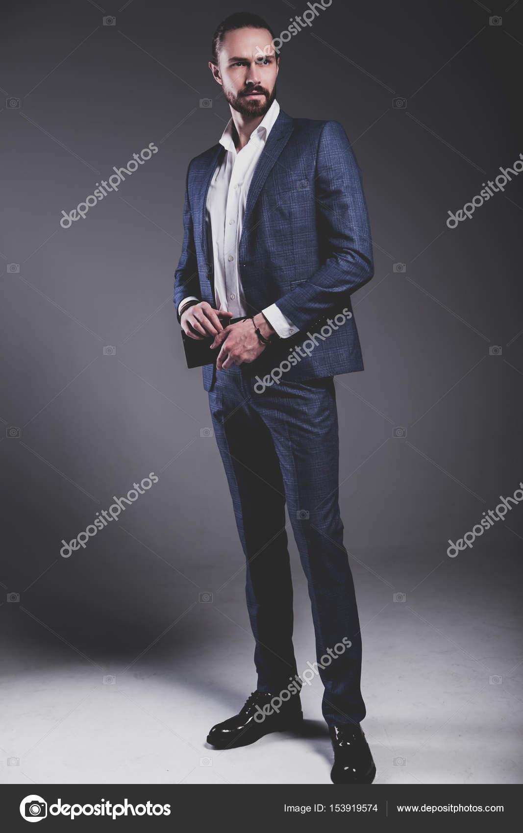 2273428a0 Retrato de guapos moda hipster estilo empresario modelo vestido con elegante  traje azul posando sobre fondo gris en estudio.
