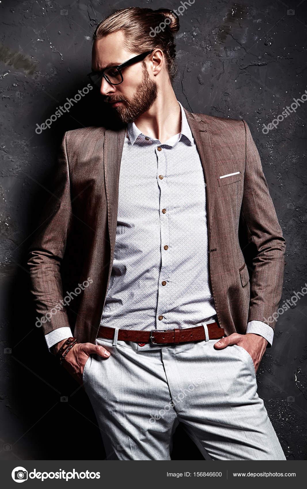 elegante lunghi maschile accanto in a muro capelli tuta mani in e tasche posa con tasche barbuti Modello occhiali scuro xedCBo