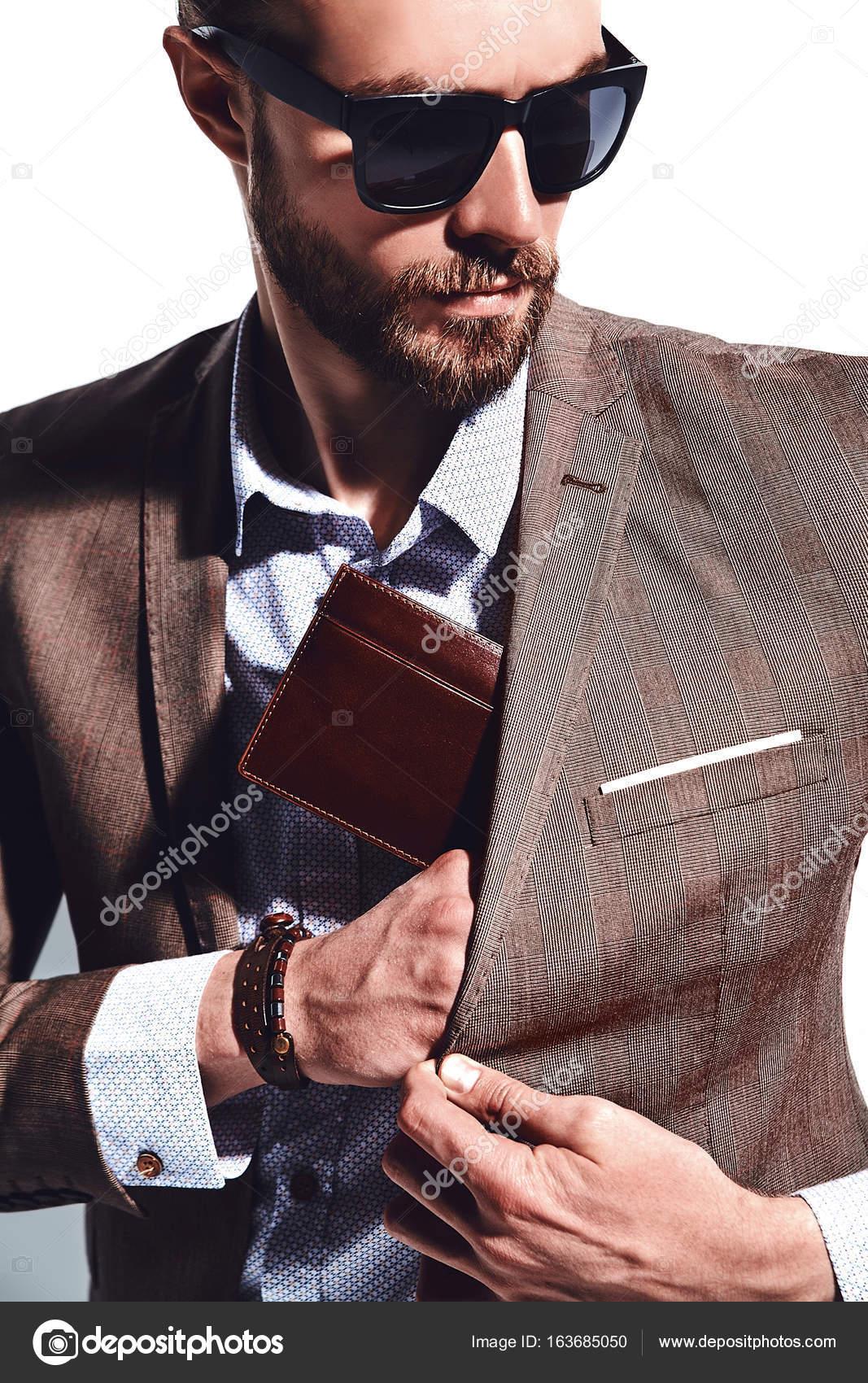 06791d4cdfd1c ... estilo empresario modelo vestido con elegante traje marrón en gafas de  sol posando junto a la pared blanca en estudio. Saca o ponga su cartera de  cuero ...