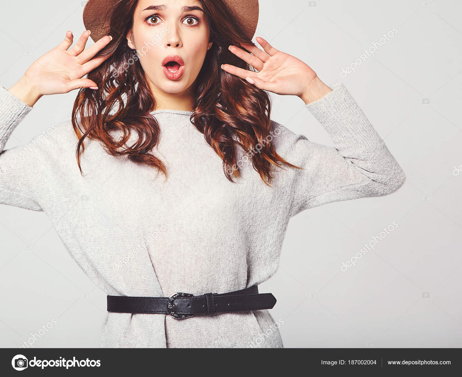 d9000369b80e Ritratto di giovane ragazza elegante modello con l espressione facciale di  sorpresa in vestiti di grigio casual estate in cappello marrone con trucco  ...