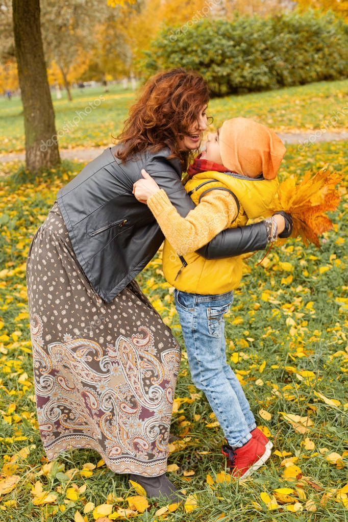 Happy Mother and Child Boy Hugging in Fall Park Outdoor
