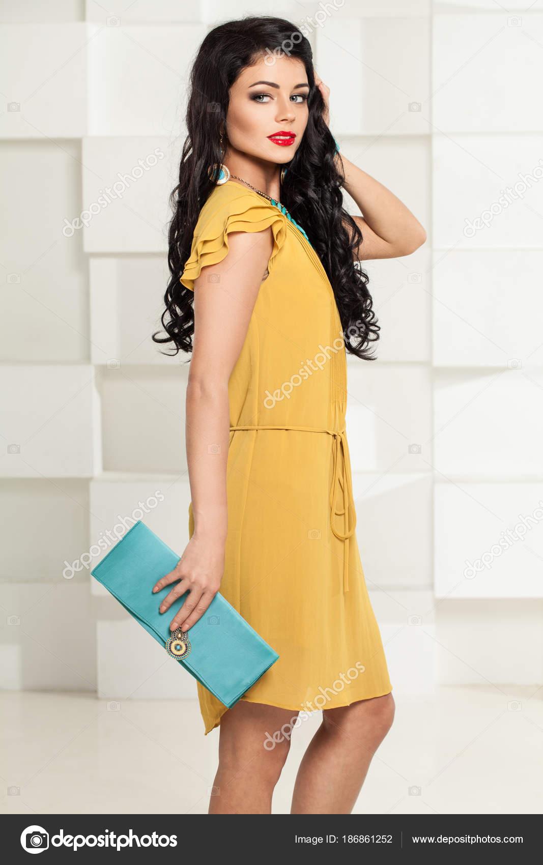 65237d3d6e3a Donna sorridente del Brunette in vestito giallo alla moda e borsa blu–  immagine stock