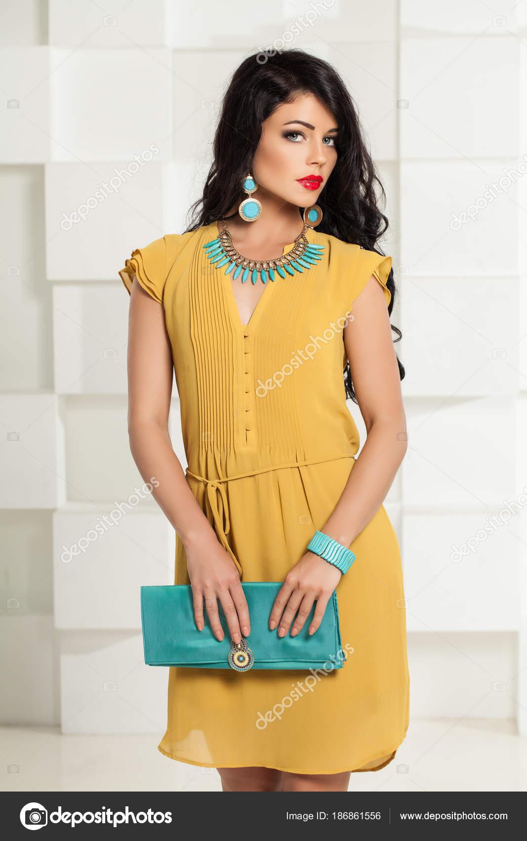 Bella donna in vestito giallo e accessori alla moda blu su sfondo bianco  Studio — Foto di ... e267a585d13